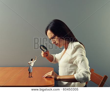 serious woman looking at small emotional woman on the table