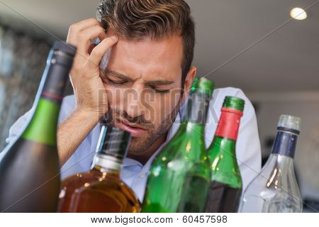 Drunk businessman slumped beside many spirit bottles at the local bar