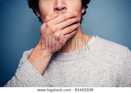 Shocked Young Man With His Hand On His Mouth