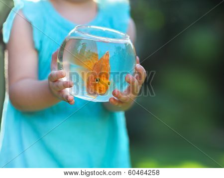 Little Baby Girl Holding A Fishbowl With A Goldfish On A Nature Background