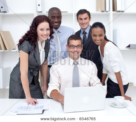 International businessteam using a laptop together in office poster