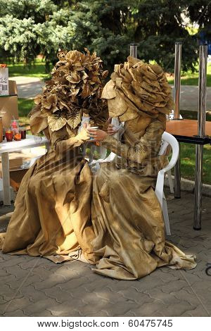 two women in mascarade gold floral dress
