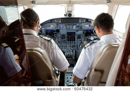 Rear view of pilot and copilot in cockpit of private jet poster