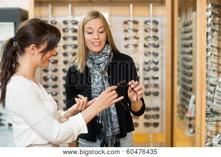 Young woman assisting female customer in selecting glasses at store