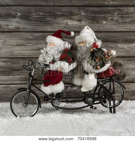 Two Funny Santa Claus On A Tandem In Hurry For Christmas Shopping.