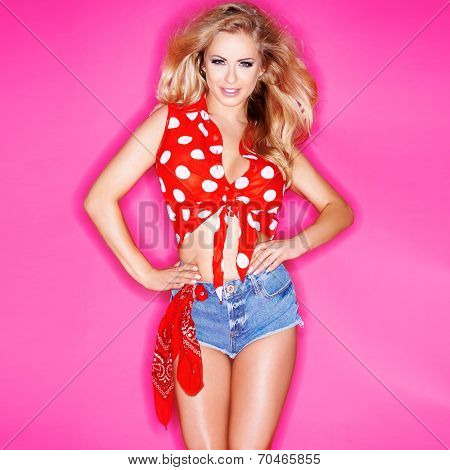 Cute beautiful blond woman in red polka dots and skimpy denim shorts  on pink