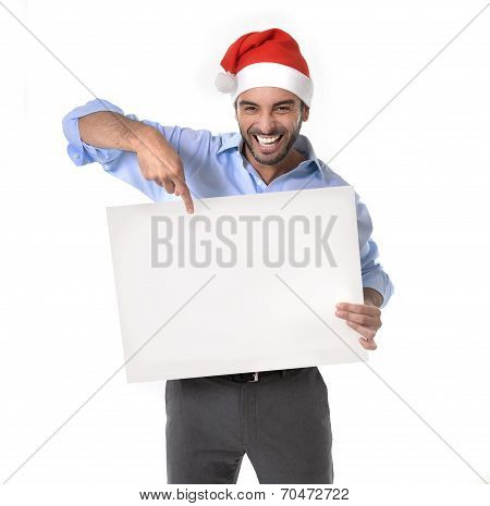 Handsome Business Man In Santa Christmas Hat Pointing Blank Billboard