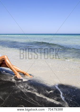 Attractive Female Legs Relaxing On A Beautiful  Beach