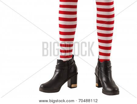 Lower half of girl wearing stripey socks and boots on white background