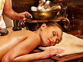 Young woman having Ayurveda stone massage. poster