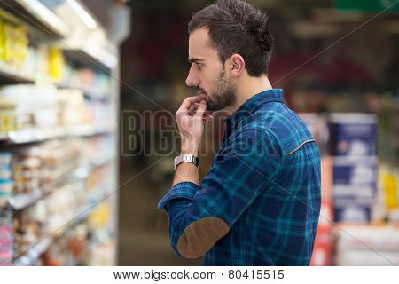 Smiling Man Buying Dairy Products In Supermarket