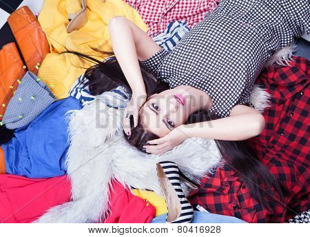 Nothing to wear concept, young attractive stressed woman lying down on a pile of clothes