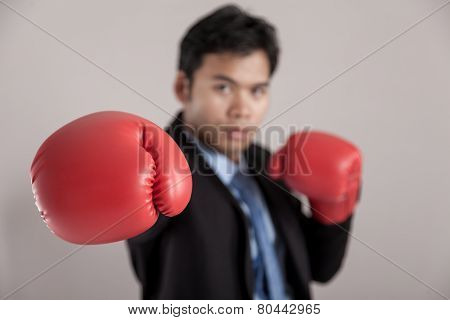Asian Businessman Punch With Red  Boxing Glove Focus At The Glove