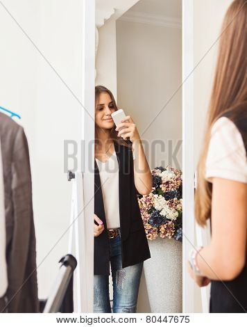 Teen Girl Making Photo With Mobile Camera In Shop