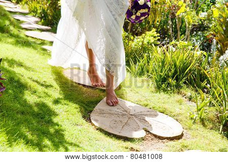 Beautiful Young Bride In A White Wedding Dress With Bouquet In Hand, Walking On A Tropical Island