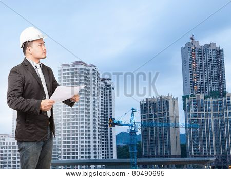 Engineering Man Wearing Western Suit And Safety Helmet With Building Plan Document Working On High S