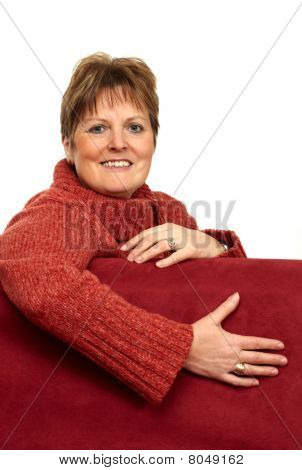 Happy Senior Woman Relaxing On Red Couch