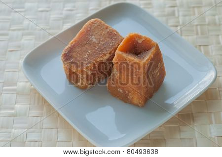 Sugarcane concentrate - an Indian jaggery cakes on white plate poster
