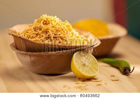 Popular street side indian snacks - Fried Sev with lime and chili