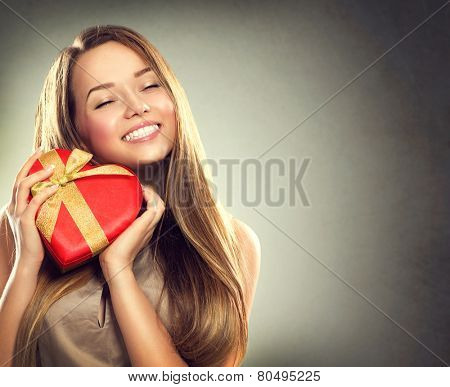 Beauty happy girl with Valentine Gift box. Smiling surprised model girl takes heart shaped red present.