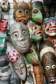 a variety of carved and painted wooden masks hanging on the wall of a store poster