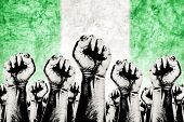Nigeria Labor movement graphic concept workers union strike concept with male fists raised in the air fighting for their rights and Nigerian national flag in out of focus background. poster