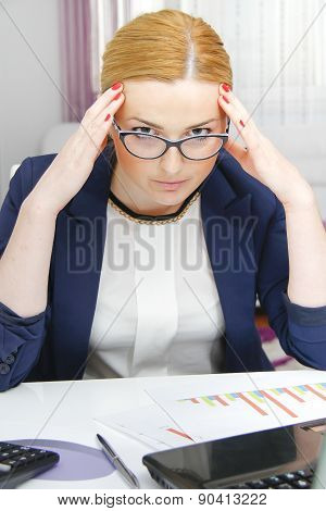 Business Woman Analyzing Investment Charts With Calculator And Laptop