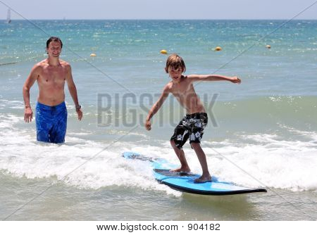 Happy Father Teaching His Young Son To Surf