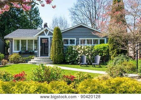 Cozy house with beautiful landscaping on a sunny day. Home exterior.