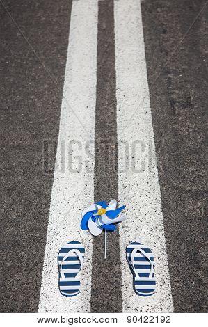 Beach slippers with pinwheel lying on grey asphalt