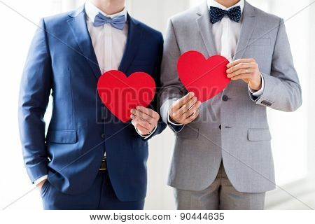 people, homosexuality, same-sex marriage, valentines day and love concept - close up of happy married male gay couple holding red paper heart shapes on wedding