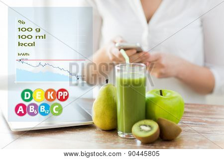 healthy eating, technology, diet and people concept - close up of woman hands holding smartphone with tablet pc, fruits and fresh juice sitting at table over calories and vitamin chart poster