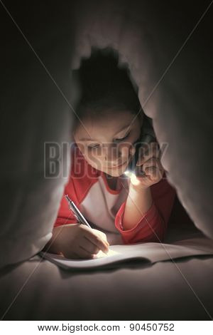 Girl reading and writing under the covers using flashlight poster
