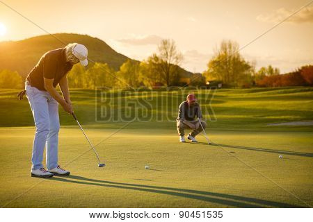 Two male golf player at sunset on green, one putting , with beautiful fairway in background.