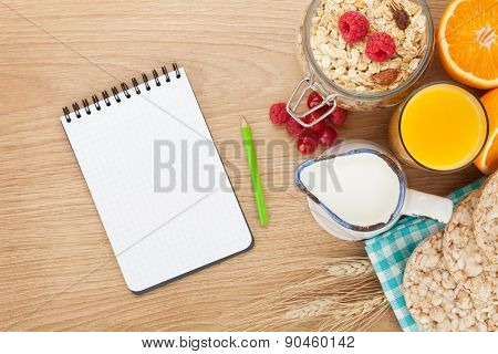 Healty breakfast with muesli, berries and orange juice. View from above on wooden table with notepad for copy space