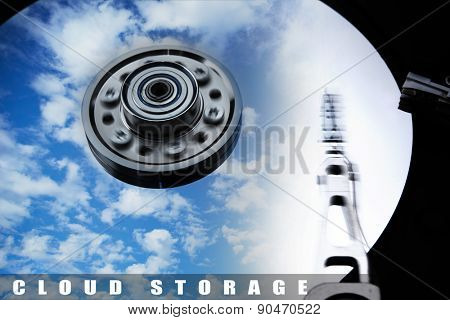 Cloud storage or cloud drive concept image. Hard disk (Hard drive) with clouds and sky reflecting on disk. Head and Axis with motion blur.