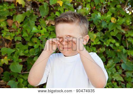 Blond little boy rubbing eyes for allergy