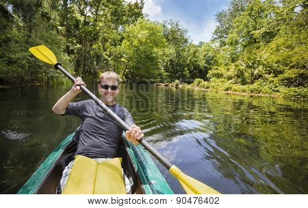Smiling, happy man kayaking along a beautiful jungle river. Lots of copy space in an active outdoor lifestyle photo