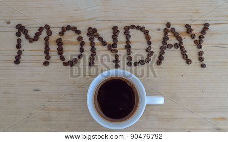 Cup of coffee on wooden background and MONDAY coffee beans