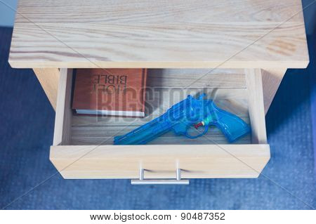 Toy Gun And Bible In Drawer