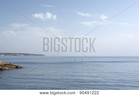 Couple paddleboarding on blue sea