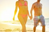 Summer beach couple romantic holding hands at sunset walking in love on honeymoon travel vacation holidays. Unrecognizable woman and man in happy romance wearing bikini and casual beachwear shorts. poster