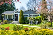 Cozy house with beautiful landscaping on a sunny day. Home exterior. poster