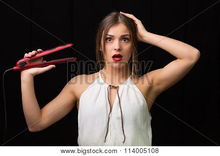 Puzzled Woman With A Flat Hair Iron