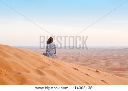 Woman Watching The Sunset In The Desert Sand