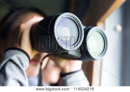 Asian woman looking though binocular