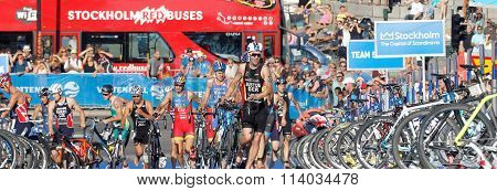 STOCKHOLM SWEDEN - AUG 23 2015: Chaotic scene with running triathletes with bicycles in the transition zone bus and sea in the background in the Men's ITU World Triathlon series event August 23 2015 in Stockholm Sweden