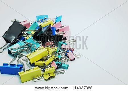 Various size and colorful paper clips. Selective focus on black at center. Gray backgrou