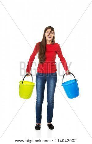 Woman holding empty plastic buckets.