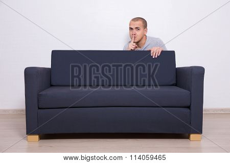 Young Man Hiding Behind A Sofa And Showing Shhh Sign
